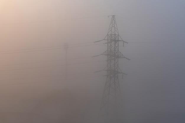 Металлическая конструкция высоковольтной линии электропередачи в окружении густого тумана атмосферный туманный пейзаж