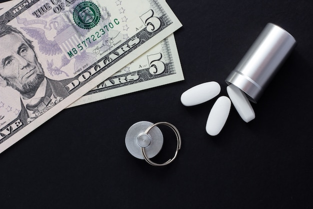 Metal container for pills and money on a black background, concept of expensive drugs, clo
