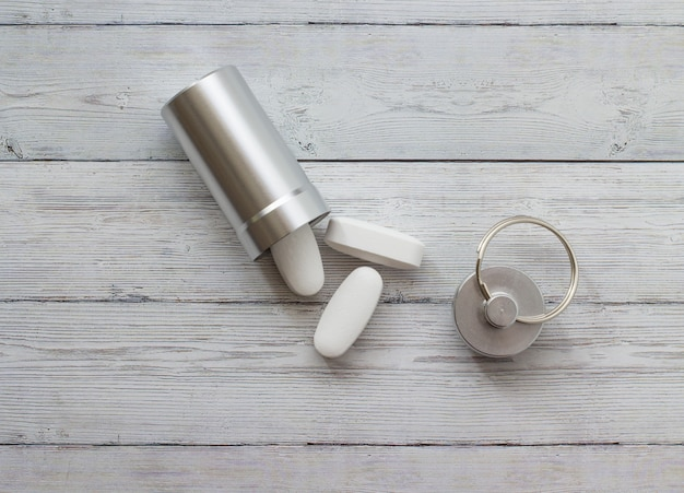 Metal container and pills on a wooden background