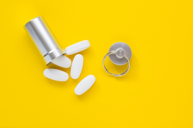 Metal container and pills on a yellow background, close-up