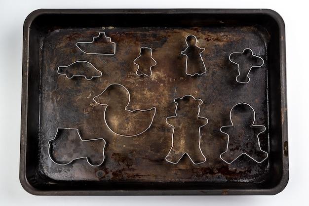 分離された古いさびた金属板に金属製のクッキーカッター