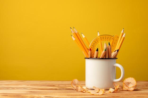 Металлическая чашка с острыми карандашами и стружкой карандаша на деревянном столе