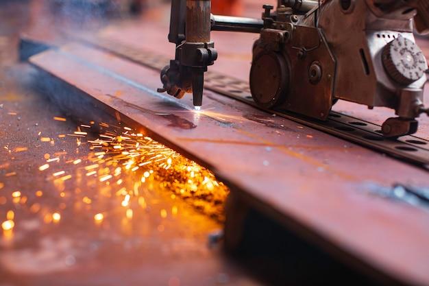 Искра резки металла на стальной пластине дна резервуара с вспышкой режущего света крупным планом в ограниченном пространстве.