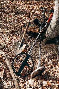숲의 땅에 금속 탐지기 장치 및 스페이드