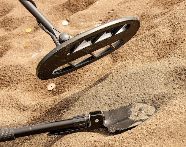 The metal detector, ring and spade on the sand