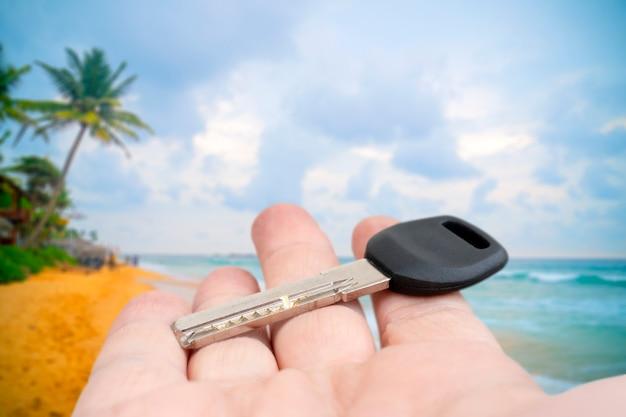 Metal door key in a man's hand. sale and rental of real estate.