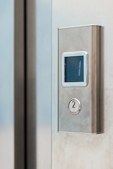 Metal elevator button with electronic display