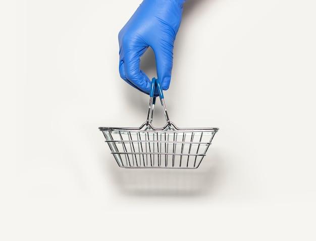 Металлическая пустая корзина для покупок в руке в защитной перчатке.
