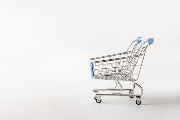 Metal empty shopping cart, trolley grocery on white.
