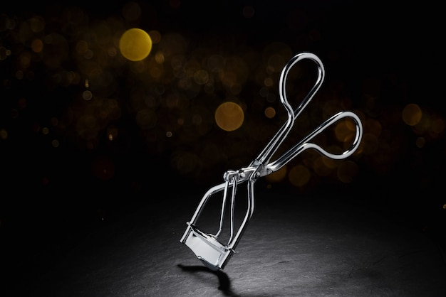 Metal eyelash curler on black wall with copy space