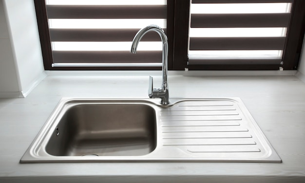 Metal faucet in the modern gray kitchen