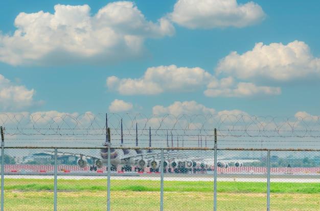 공항의 금속 울타리와 공항 주차장에 흐릿한 비행기가 주차되어 있습니다. 코로나바이러스로 인해 많은 비행기가 주차되고 항공편이 영향을 받습니다. 항공 비즈니스 위기입니다. 푸른 하늘에 대 한 울타리입니다.