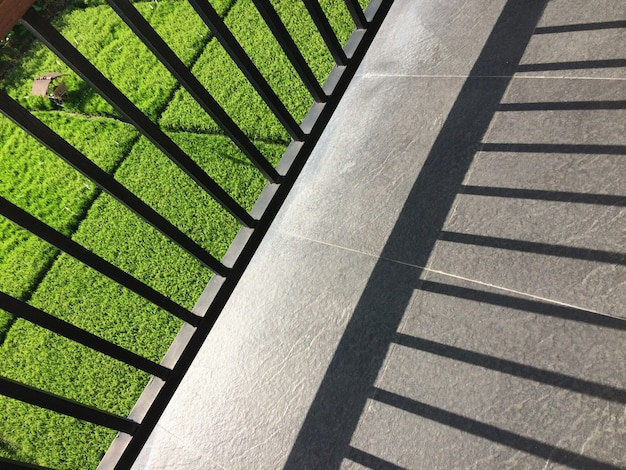 Metal fence shadow on the balcony with a view of a grassy field on a sunny day