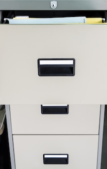 Metal file cabinet with open drawer.