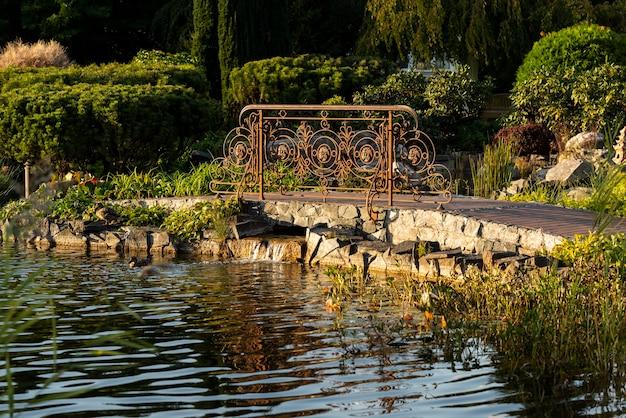 領土のランドスケープデザインの人工貯水池の近くの公園にある金属鍛造の彫刻が施された手すり