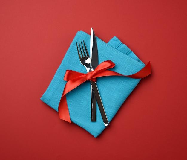 Металлическая вилка и нож, перевязанные красной шелковой лентой