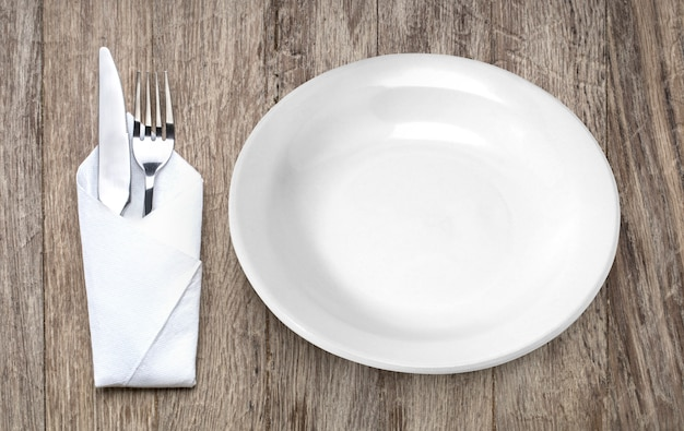 Metal fork and knife on wooden table