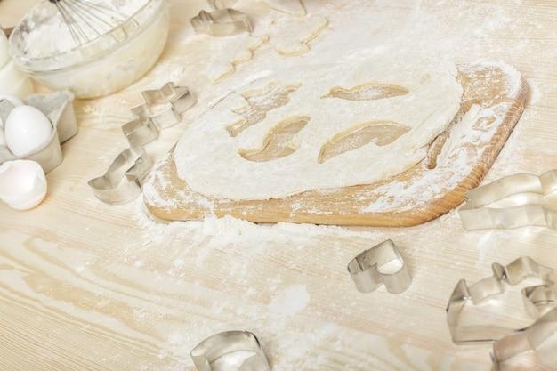 テーブルの上のクッキーと生の生地のための金属フォーム