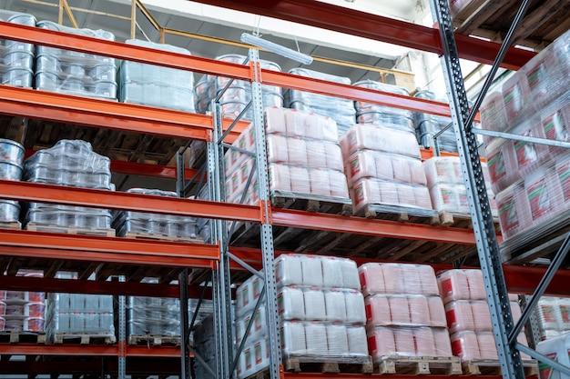 Полки с металлическим каркасом, заполненные упакованными канистрами и контейнерами, завернутыми в полиэтилен на деревянных поддонах