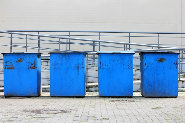 Metal garbage containers are arranged in a row.