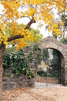 黄色い秋の木の下の石の柵の金属の門