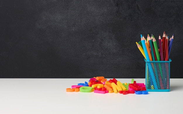 Metal glass with pens, pencils and felt-tip pens and scissors on the background of an empty black chalk board, white table, copy space