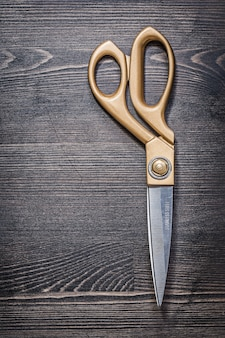 Metal golden scissors on vintage wooden board vertical image