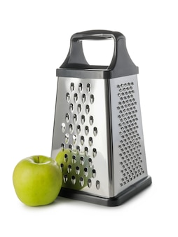 Metal grater and apple on white background