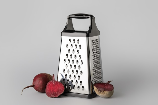 Metal grater and beetroots on grey background