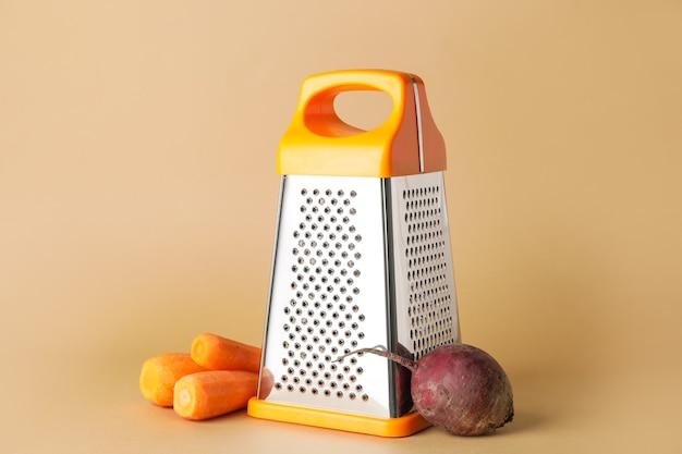 Металлическая терка, морковь и свекла на цветном фоне