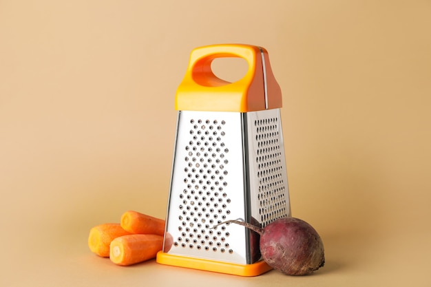 Metal grater, carrots and beetroot on color background