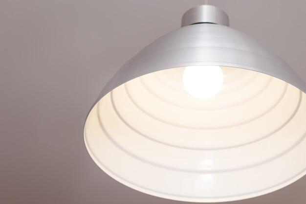 Металлический серый светильник висит на кабеле.