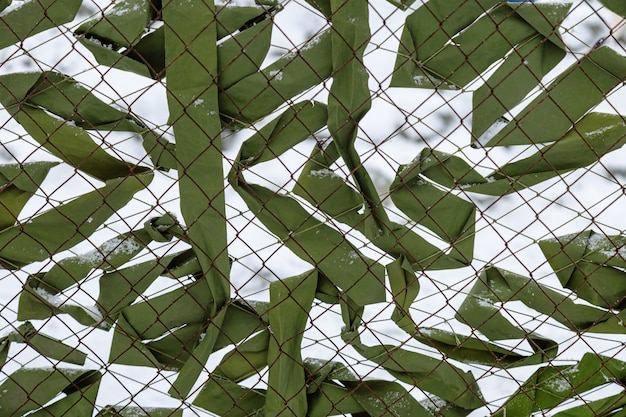 Metal grid fence with camouflage textile