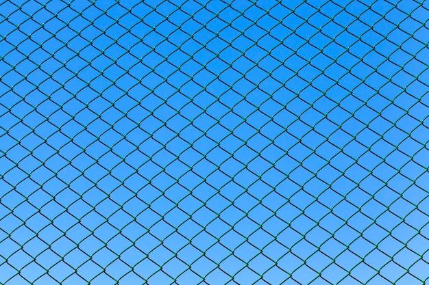 Металлический гриль на фоне голубого неба, огороженная территория