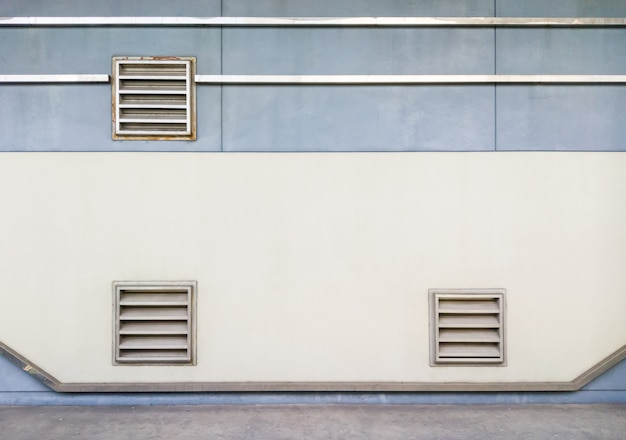 Metal grille of the ventilation system on the concrete wall.