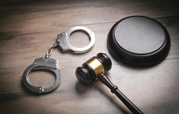 木製の背景に金属製の手錠と裁判官のガベル。