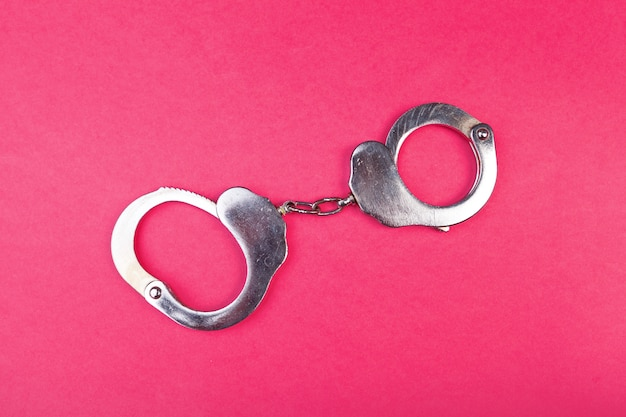 Metal handcuffs on bright pink  top view