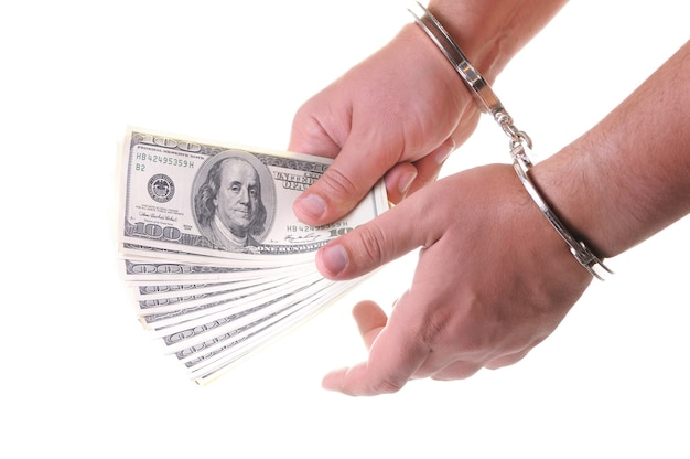 Металлические наручники, руки и деньги на белом фоне, концептуальная серия