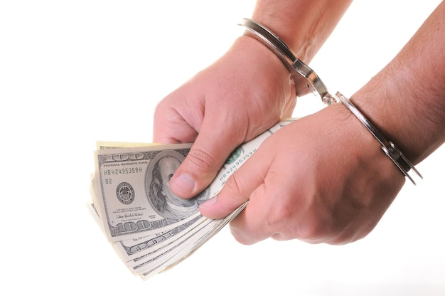 Metal handcuffs, hands, and money on white