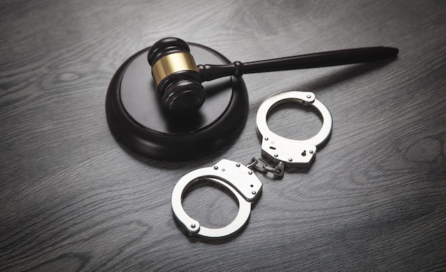 Metal handcuffs and judge gavel on the dark background.