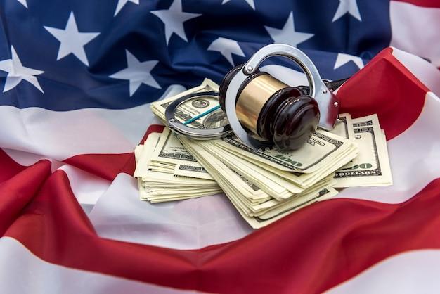 金属製の手錠、裁判官のハンマー、アメリカの旗の上にあるドル紙幣。金融犯罪または汚職の概念