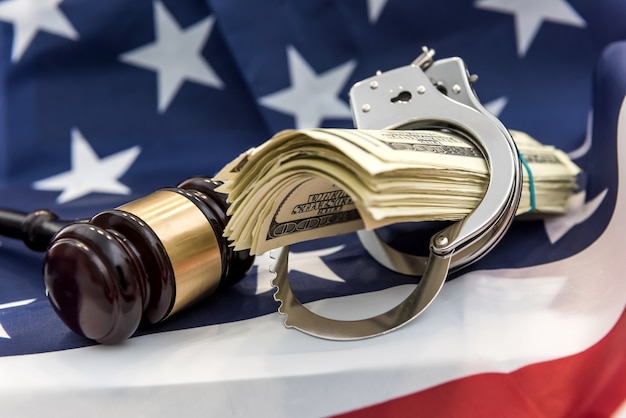 Metal handcuffs, judge's hammer and dollar bills lying on flag of american. financial crimes or corruption concept