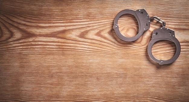 木製の背景に金属の手錠。
