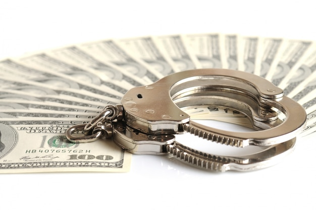 Metal handcuffs and stack of banknotes