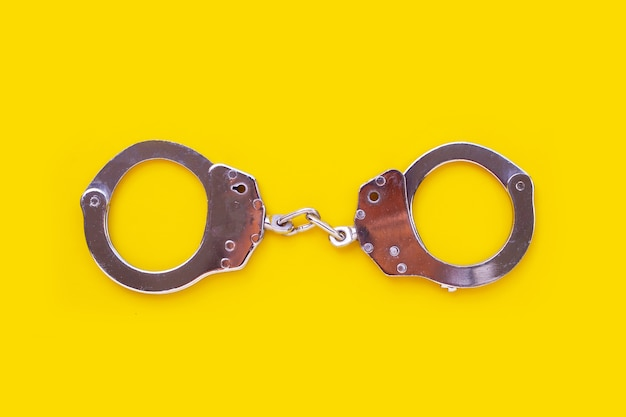 Metal handcuffs on yellow background