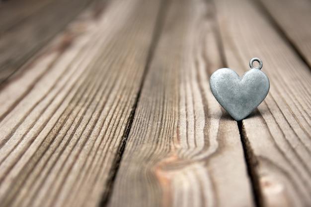 木製の背景に金属の心幸せなバレンタインデーの愛