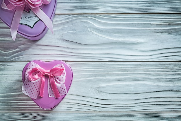 Metal heart-shaped small present boxes on wooden board