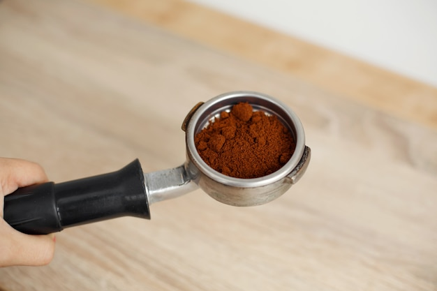 Metal holder for the coffee machine with ground coffee inside lies on a wooden table