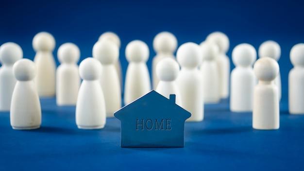 개념적 이미지에서 사람들을 대표하는 나무 인형으로 금속 집 모델