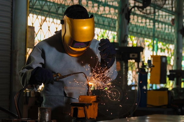Metal industry welders in industrial plants standard protective equipment, gloves and masks.